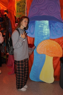 Junior Sophie Comeau poses next to the Alice in Wonderland themed props in the main hallway.
