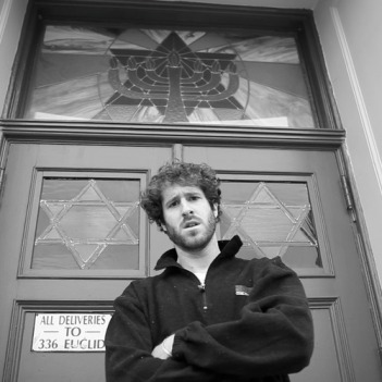 """Burd standing in front of a synagogue as part of his """"All K"""" video"""
