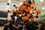Seniors rushing under the balloons after their win