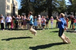 Students jump for the potato sack portion of the race.