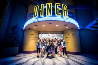 Teens pose in front of Universal Orlando diner.